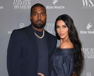 Kanye West sourit à la caméra, alors qu'il assiste à un événement en compagnie de son amoureuse, Kim Kardashian West.