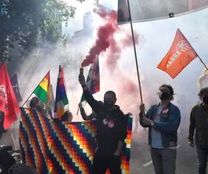 Un homme tient une torche de fumée lors d'une manifestation marquant la Journée internationale des travailleurs à Barcelone le 1er mai 2021