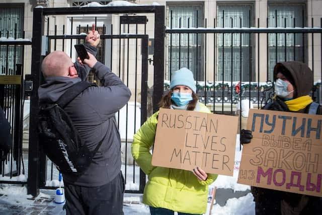 Un manifestant se photographie en train de faire un doigt d'honneur en direction du consulat.