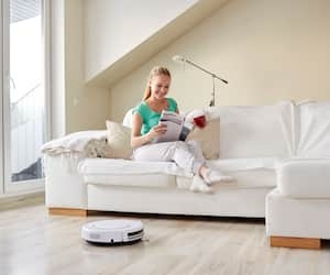 happy woman and robot vacuum cleaner at home
