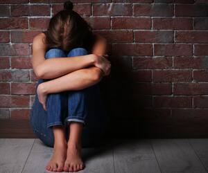 Battered young woman sitting near brick wall
