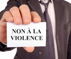 Homme tenant une carte sur laquelle est écrit non à la violence