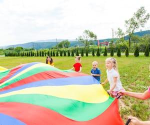 Rainbow parachute held by children
