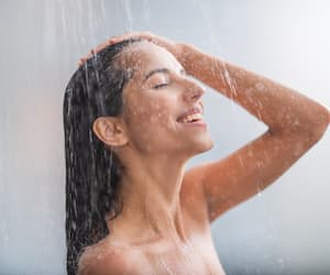 Positive woman taking hot shower