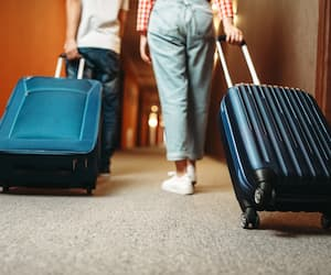 Couple with suitcase walking by the hotel corridor