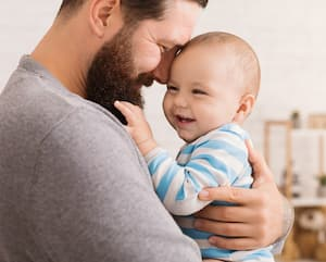 Loving father embracing his cute baby son