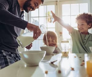 Smiling father pouring milk in to bowls for breakfast