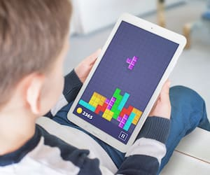 Classic tetris game on tablet in boy hand.