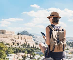 Young woman using smart phone in Athens with Acropolis at the background. Traveler girl enjoying vacation in Greece. Summer holidays, vacations, travel, tourism, technology concept.