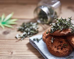 Delicious homemade cookies with a garnish of hemp leaves. Space for text.