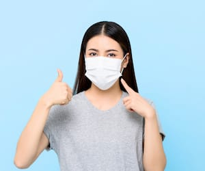 Young Asian woman wearing face mask protecting Coronavirus and allergies giving thumbs up isolated on light blue background