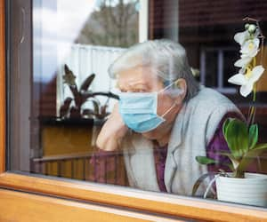 Senior woman with surgical mask sitting on a window at home, coronavirus and covid-19 provisions