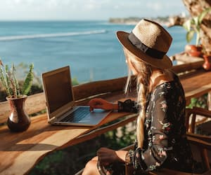 Business woman working with computer on the beach. Freelance concept. Pretty young woman using laptop in cafe on tropical beach