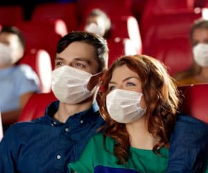 couple in masks watching movie in theater