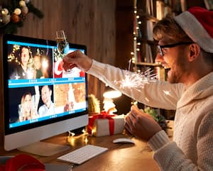Young man wears Christmas hat celebrates Happy New Year by video call.