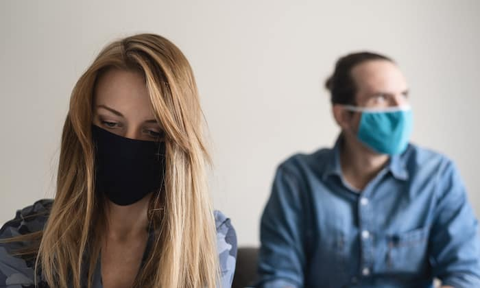 An stressed couple in self-isolation wearing a face mask. Family problems during quarantine.
