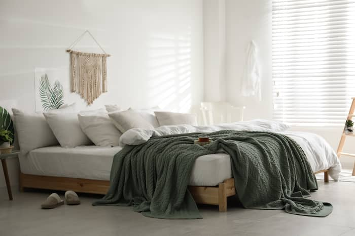 Comfortable bed with warm knitted plaid in stylish room interior