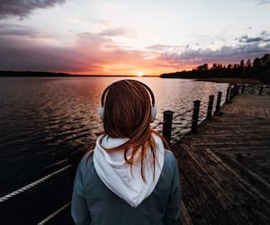 The girl listens to music with headphones stands on the pier near the lake and looks at the sunset,ASMR concept