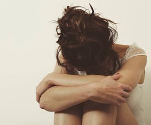 femme triste contre un mur