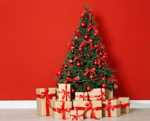 Decorated Christmas tree and gift boxes near red wall. Space for text