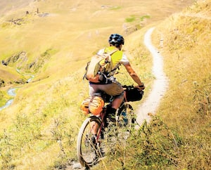 Mountain biker is travelling in the highlands of Tusheti region, Georgia