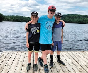 Léo, à gauche, avec ses amis Thomas et Olivier devant le Lac-aux-Sables, en Mauricie, va s'ennuyer du camp de vacances.