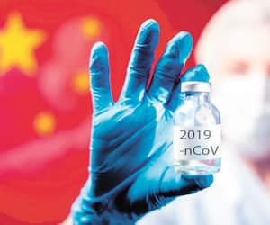 A doctor in blue medical gloves and mask holding an ampula with vaccine in front of flag of China. Close up shot. Coronavirus, epidemic and medicine concept.