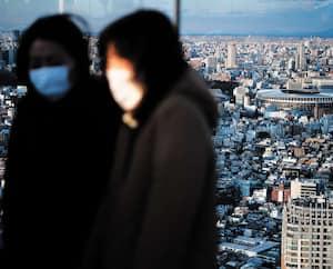 Deux Japonais portant un masque pour se protéger du coronavirus sont photographiés devant le nouveau stade olympique de Tokyo, qui doit accueillir les Jeux olympiques d'été, dès le mois de juillet.