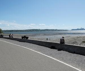 Les visiteurs étaient déjà de retour sur l'île d'Orléans, vendredi. On voit des personnes profiter du bord du fleuve, à Sainte-Pétronille.