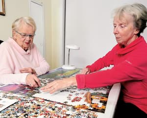 Liette Desjardins aide sa mère, Camille Hudon, à faire un casse-tête à leur domicile de Sainte-Anne-de-la-Pocatière. L'aînée de 89ans vit avec de graves problèmes de vision et pourrait devoir attendre troisans avant d'être opérée aux yeux, en raison du délestagedû à la pandémie de COVID.