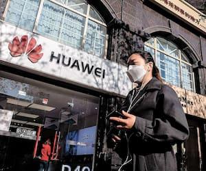 Une femme portant un masque pour lutter contre la Covid-19 marche devant une boutique de la compagnie de télécommunication d'Huawei à Pékin, le 22 avril dernier.