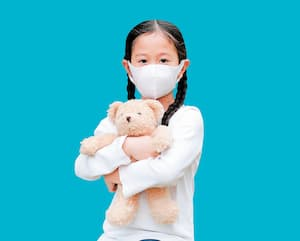 Coronavirus covid-19 and pollution protection concept. Asian little kid girl hugging teddy bear doll with wearing mask to against corona virus and air pollution pm2.5 isolated on blue with copy space