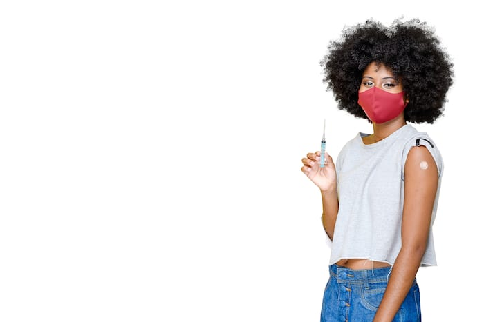young teenager wearing a covid-19 protective mask being vaccinated COVID-19