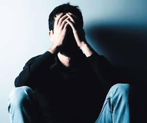 sad man sitting on ground on dark background