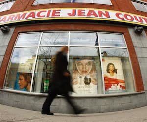A pedestrian walks past a Jean Coutu pharmacy in downtown Montreal
