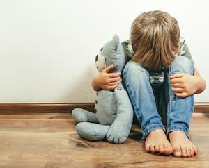 Sad depressed boy with teddy bear