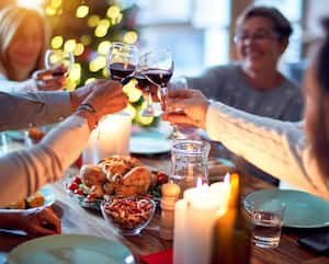 Family and friends dining at home celebrating christmas eve with traditional food and decoration, all sitting on the table together