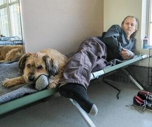 Dave Arbic préfère dormir avec son chien Benji sur un lit de camp dans un centre communautaire plutôt que d'aller à l'hôtel qui lui est offert gratuitement par la Croix-Rouge.