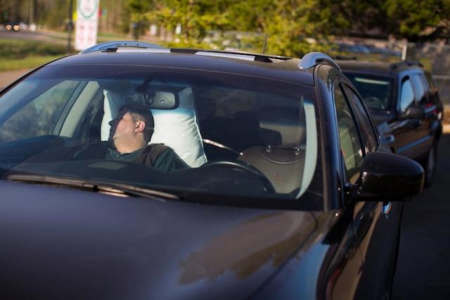 Un citoyen de Fort McMurray dort dans une voiture dans la communauté d'Anzac, mercredi, après le lancement de l'ordre d'évacuation.