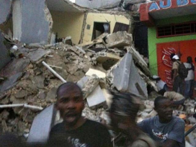 Cette photo obtenue de Twitter nous montre un groupe d'Haitiens devant un édifice qui s'est effondré.
