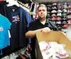 Le propriétaire de la Boutique Hockey.com, Allan Beaupré, montre une boîte de tuques du Canadien qu'il n'a pas été capable de vendre.