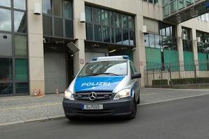 Une voiture de police quitte un établissement judiciaire de Berlin avec Luka Rocco Magnotta à bord. On remarque aussi la photo prise par les autorités allemandes après son arrestation.