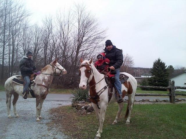 Adam Prémont accompagné de sa fille de trois ans sur la jument Ruby. Il y a aussi un ami du propriétaire qui chevauche l'autre jument, Shelsy.