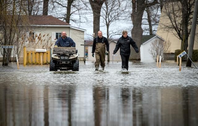 La Ville de Rigaud, en Montérégie, a déclaré l'état d'urgence jeudi en raison de la crue printanière «historique» causant d'énormes inondations sur son territoire, à Rigaud près de Montréal, samedi le 22 avril 2017. Sur cette photo: Des résidents marchent près du chemin de la Baie Quesnel.  JOEL LEMAY/AGENCE QMI