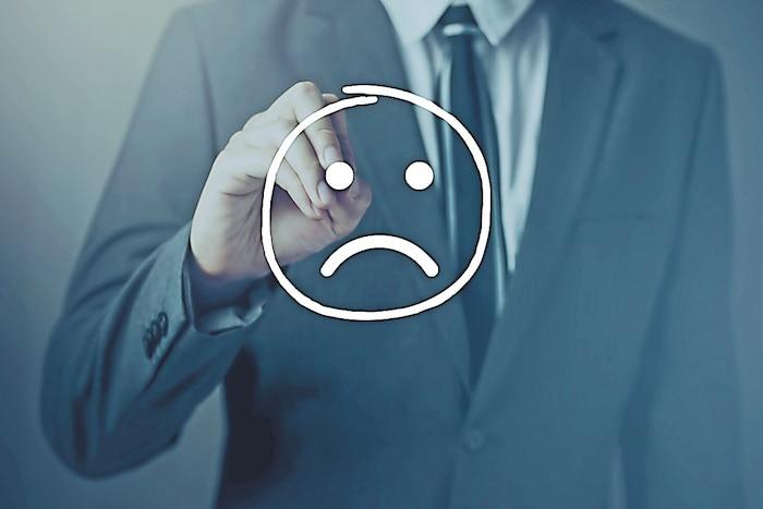 Businessman writing unhappy face on virtual screen