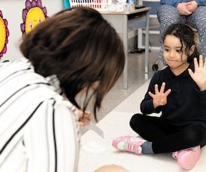 L'enseignante Nadira Azzoug, à l'école Saint-Noël-Chabanel de Montréal, présente des dessins de mains montrant un chiffre, qu'une petite élève de 4 ans imite. « C'est une activité d'éveil aux maths, mais on travaille aussi le tour de rôle, la communication, à travers cet atelier », explique-t-elle.