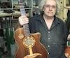 Le luthier Yvon Robert tenant entre ses mains deux de ses créations favorites.