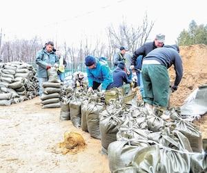 Des travailleurs agricoles guatémaltèques ont mis la main à la pâte la semaine dernière pour aider à remplir des milliers de sacs de sable pour des citoyens d'Oka aux prises avec la crue des eaux.