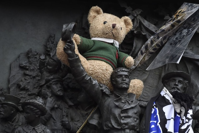 TOPSHOT - A teddy bear is lodged on the relief sculpture at the base of the statue of Marianne at Place de la Republique (Republic square) where a remembrance rally was held on January 10, 2016 to mark a year since 1.6 million people thronged the French capital in a show of unity after attacks on the Charlie Hebdo newspaper and a Jewish supermarket. Just as it was last year, the vast Place de la Republique will be the focus of the gathering as people reiterate their support for freedom of expression and remember the other victims of what would become a year of jihadist outrages in France, culminating in the November 13 coordinated shootings and suicide bombings that killed 130 people and were claimed by the Islamic State (IS) group. AFP PHOTO / DOMINIQUE FAGET / AFP / DOMINIQUE FAGET