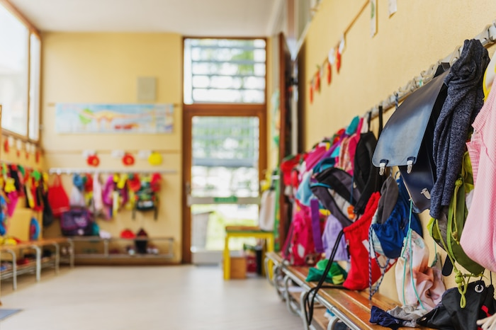 Empty hallway in the school, backpacks and bags on hooks, bright recreation room
